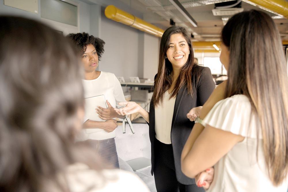 mujer hablando con compañeros de trabaji