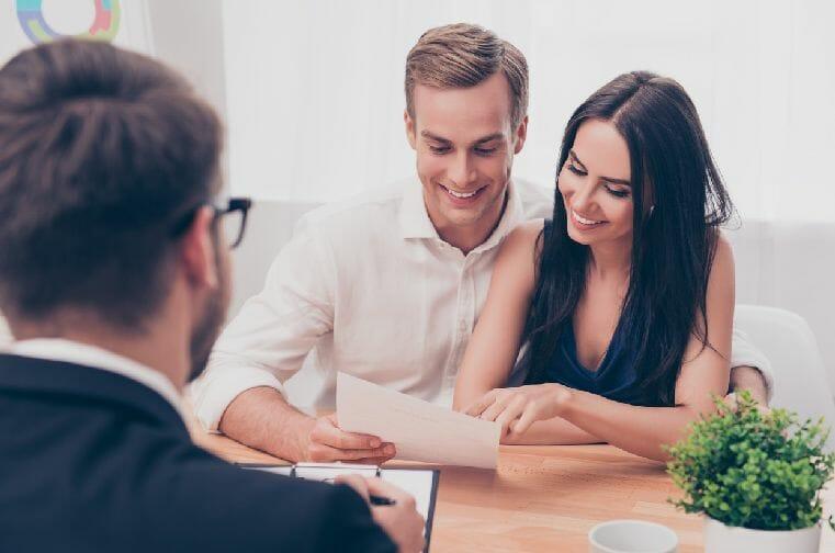 Pareja firmando un contrato de arrendamiento - Beneficios de tener un seguro de arrendamiento